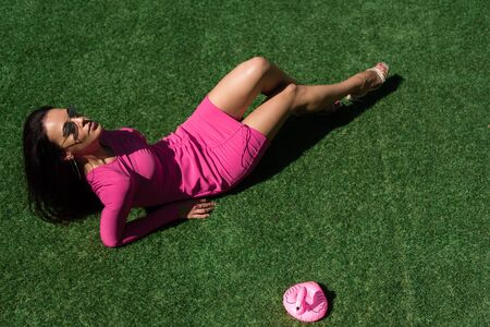 high angle view of attractive woman in dress and sunglasses posing and lying on grass outside Reklamní fotografie