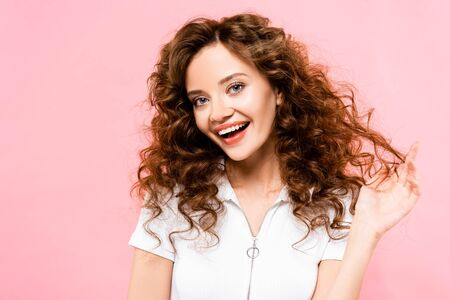 beautiful happy curly girl looking at camera, isolated on pink Reklamní fotografie