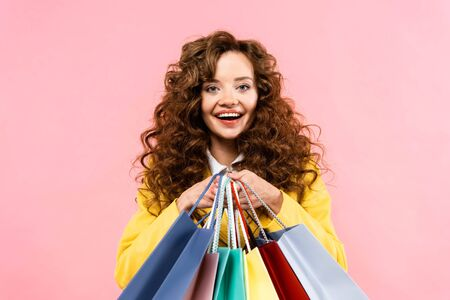beautiful curly girl holding shopping bags, isolated on pink Reklamní fotografie