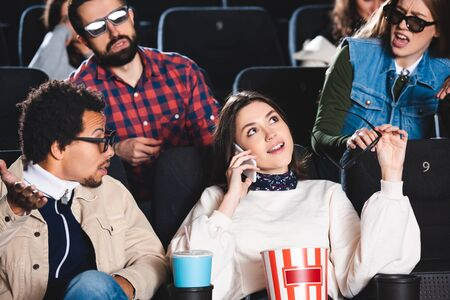 attractive woman talking on smartphone and multiethnic friends talking to her in cinema Reklamní fotografie