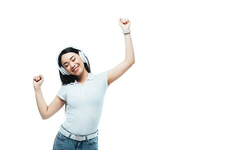smiling attractive asian girl dancing in headphones isolated on white Reklamní fotografie