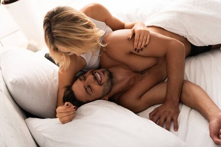 attractive tender woman hugging laughing man in bed in the morning