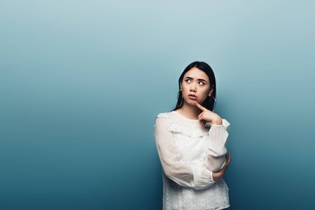 thoughtful brunette asian woman looking away on blue background