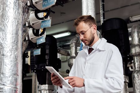 bearded engineer in white coat pointing with finger at digital tablet near air supply system