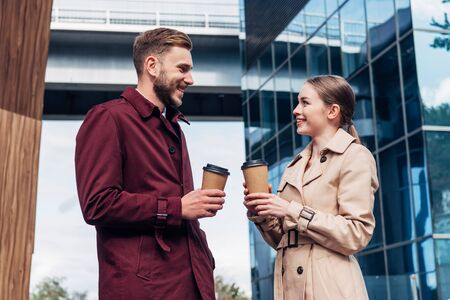 attractive woman looking at handsome man with coffee to go