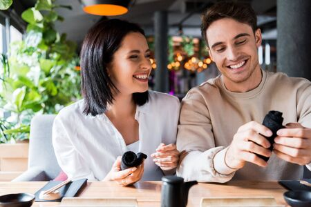 cheerful man and woman holding black napkins in sushi bar