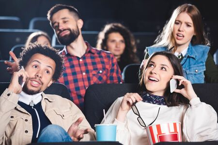 selective focus of multiethnic friends taking on smartphone and smiling in cinema Reklamní fotografie
