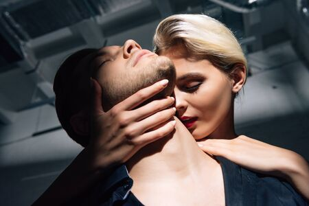 low angle view of attractive woman with red lips hugging man