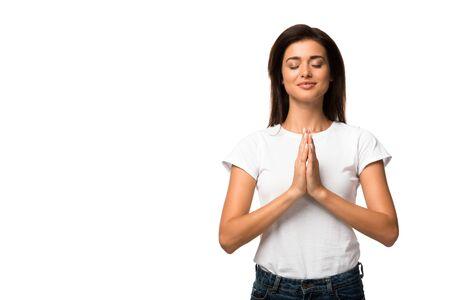 Mujer atractiva en camiseta blanca rezando con las manos juntas, aislado en blanco
