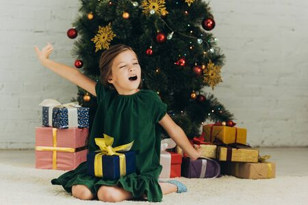 sleepy child sitting on floor with gift box, yawning and stretching with closed eyes