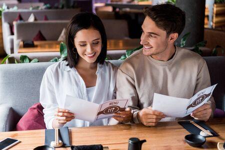 handsome man looking at happy woman smiling holding holding menu Zdjęcie Seryjne