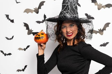 angry woman in witch hat holding pumpkin in Halloween Stok Fotoğraf