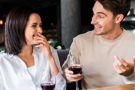 happy man looking at woman laughing while holding glasses with red wine