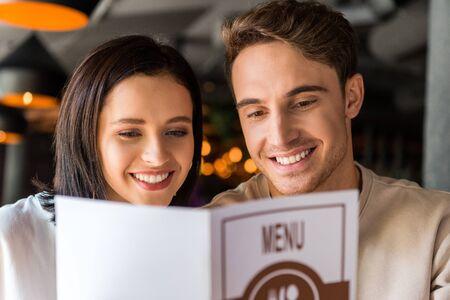 selective focus of happy man and cheerful woman holding menu Zdjęcie Seryjne