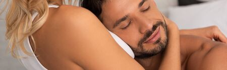 handsome man with closed eyes hugging woman in the morning Stock Photo