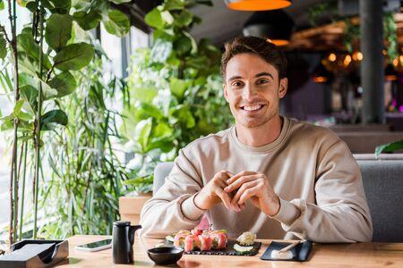 cheerful man sitting in sushi bar near tasty meal
