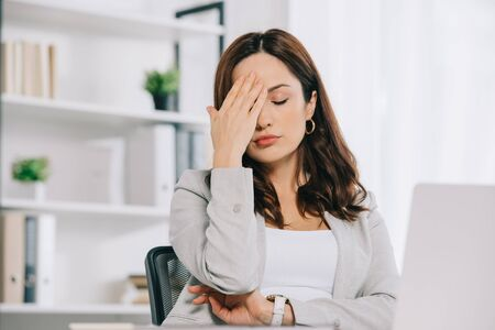 exhausted secretary suffering from headache while sitting with closed eyes and holding hand near head
