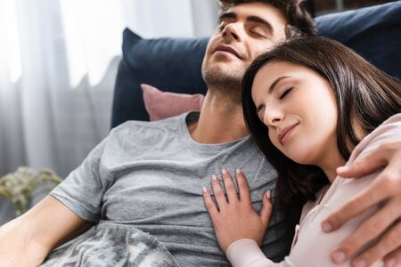 attractive girlfriend and handsome boyfriend with closed eyes hugging and lying in bed