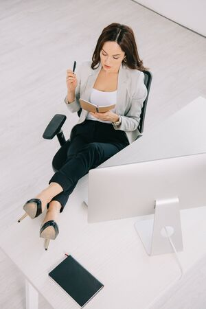 high angle view of young, concentrated secretary looking at notebook while sitting at workplace