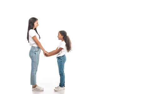 side view of happy african american mother and daughter holding hands and looking at each other on white background Stok Fotoğraf