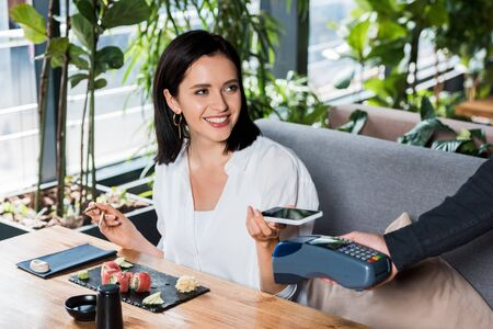 cropped view of waiter holding credit card reader near cheerful woman paying with smartphone