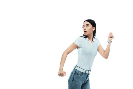 scared attractive asian girl running away isolated on white