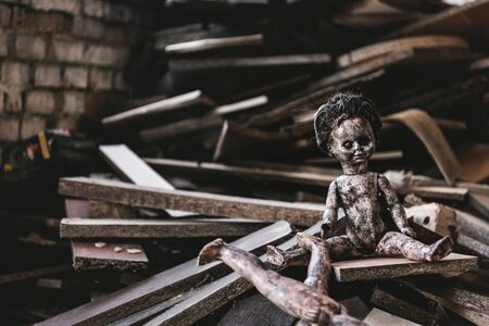 burnt and scary baby doll near damaged toy and wooden boards, post apocalyptic concept