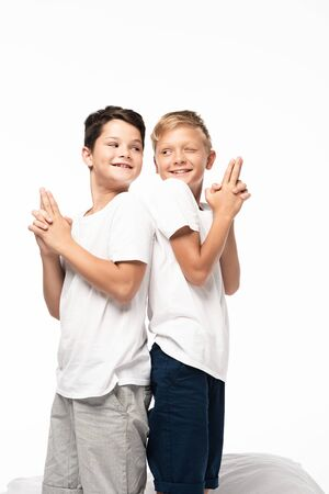 two cheerful brothers standing back to back and showing gun gestures isolated on white