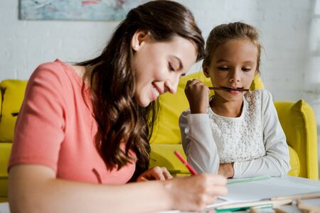 selective focus of positive babysitter drawing near cute kid in living room