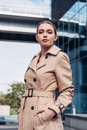 attractive woman in trench coat standing with hands in pockets Stock Photo