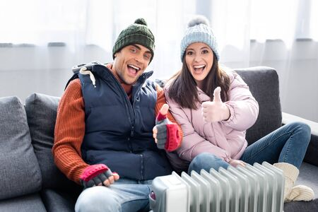 smiling girlfriend and boyfriend in winter outfit showing thumbs up and warming up near heater Stock fotó