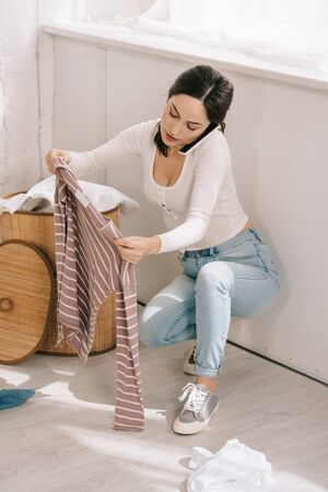 young housewife talking on smartphone while holding stripped pullover near laundry basket