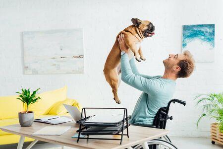 Lächelnder behinderter Mann, der französische Bulldogge im Wohnzimmer hochhält Standard-Bild