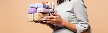 panoramic shot of pregnant woman in grey dress holding gifts isolated on beige