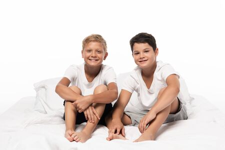 two cheerful brothers sitting on bed and looking at camera isolated on white