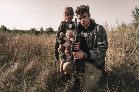 handsome man holding gun near cute kid with soft toy in field, post apocalyptic concept