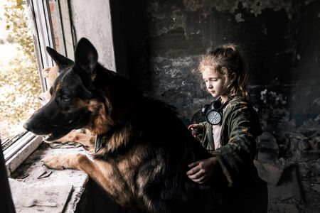 selective focus of kid touching german shepherd dog in abandoned building, post apocalyptic concept Stock Photo