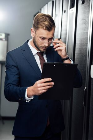 handsome businessman touching glasses while looking at clipboard