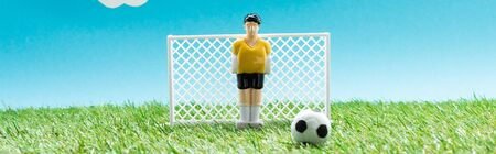 panoramic shot of toy goalkeeper near gates and ball on blue background, sports betting concept
