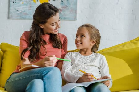 selective focus of happy kid holding notebook and looking at cheerful babysitter with pencil in living room
