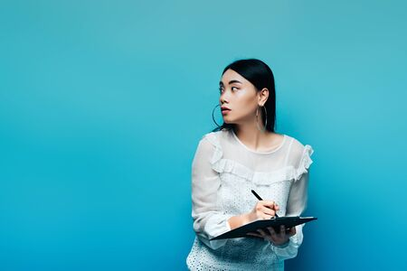 happy asian journalist in white blouse writing on clipboard and looking away on blue background