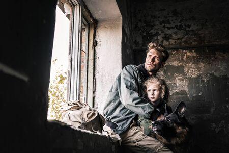 man hugging dirty kid near german shepherd dog in abandoned building, post apocalyptic concept Archivio Fotografico