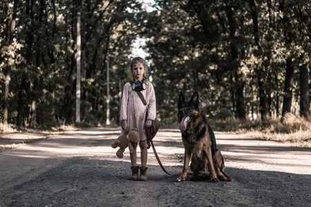 bambino sconvolto in piedi sulla strada con orsacchiotto e cane pastore tedesco, concetto post apocalittico Archivio Fotografico