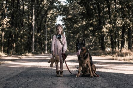 upset kid standing on road with teddy bear and german shepherd dog, post apocalyptic concept Stock Photo