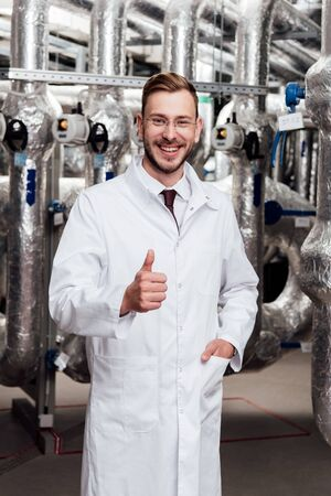 happy engineer in glasses and white coat standing with hand in pocket and showing thumb up