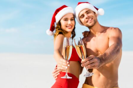 selective focus of sexy girlfriend and boyfriend clinking with champagne glasses and hugging on beach in Maldives Stock Photo