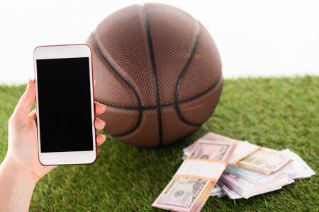 Ausgeschnittene Ansicht der weiblichen Hand mit Smartphone in der Nähe von Geldpaketen und Basketballball auf grünem Gras isoliert auf weiß, Sportwetten-Konzept