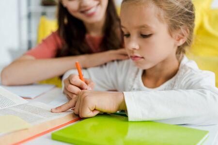 El enfoque selectivo de niño lindo apuntando con el dedo al libro cerca de la niñera feliz en casa Foto de archivo