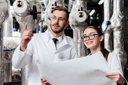 bearded engineer in glasses pointing with finger near happy coworker holding blueprint