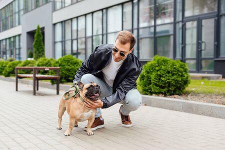 Handsome man stroking french bulldog on street